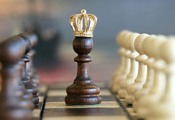A chess pawn in the middlw of the chess board with a gold crown, emulating the queen piece.
