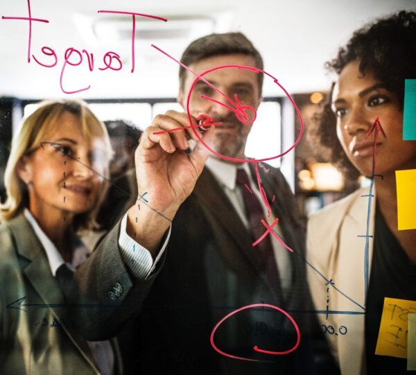 Man in suit watched by two business woman drawing a plan onto a transparent board/glass